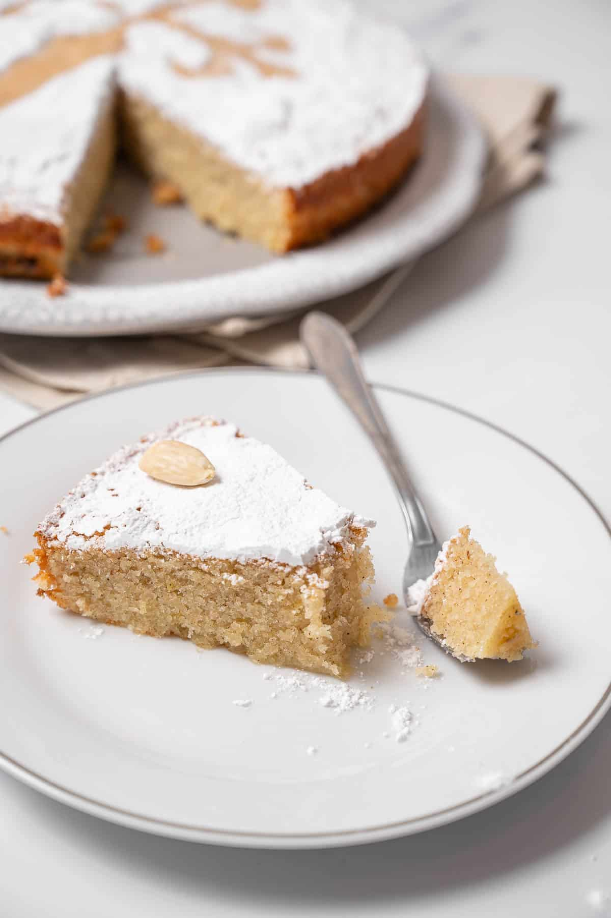 Spanish almond cake slice on a white plate with a bite taken on a fork.