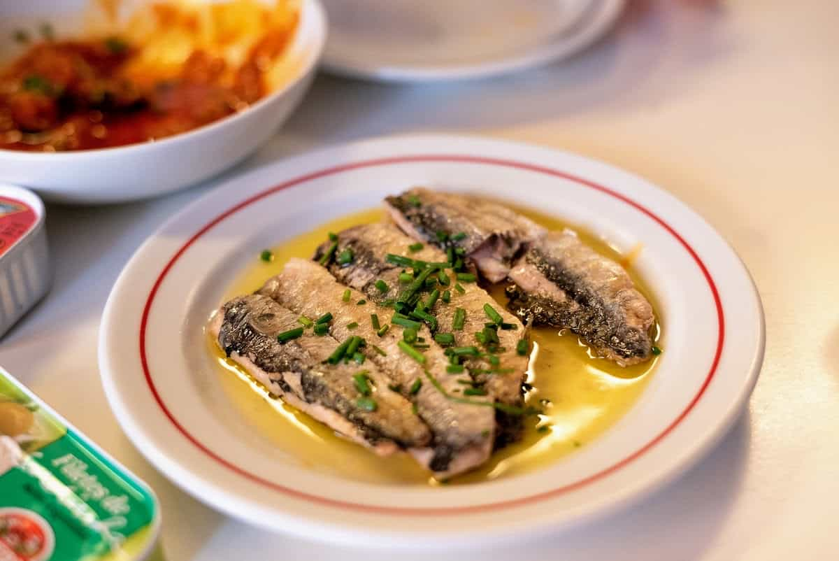 Plate of preserved fish slices in olive oil and topped with herbs.