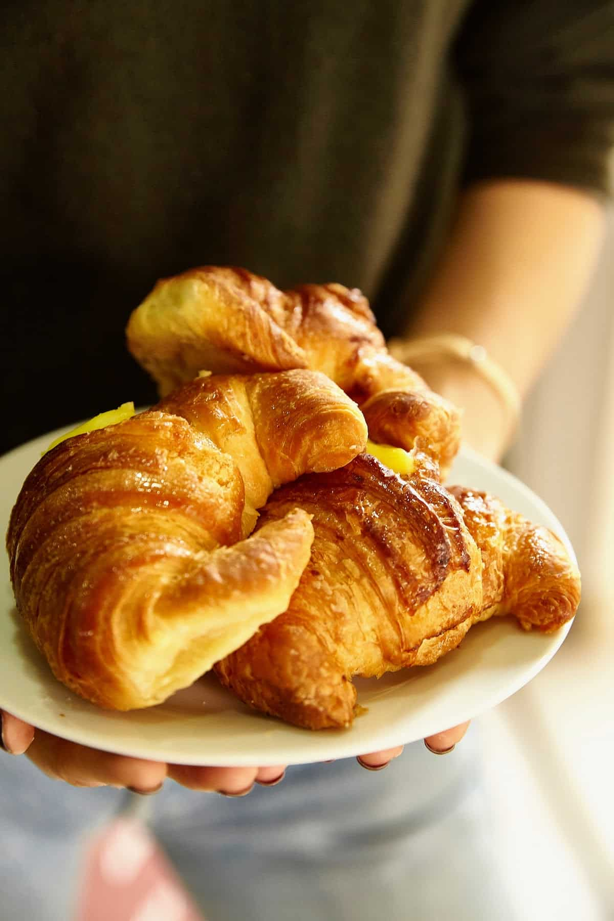 Close up of a person holding a white plate with three croissants