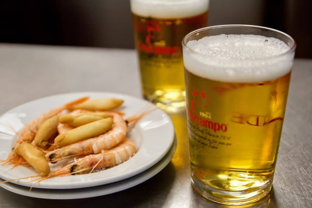Two small draft beers next to a tapa of boiled shrimp and crunchy breadstick crackers.