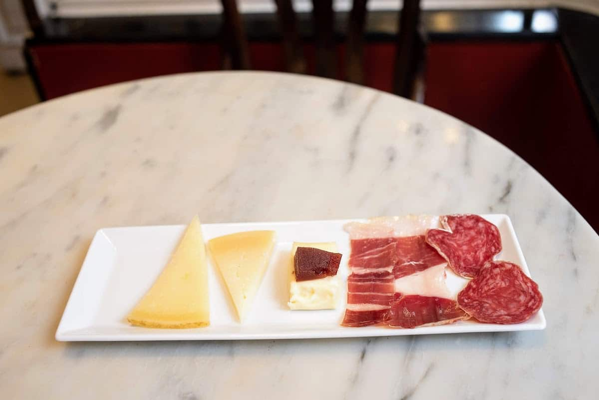 Slices of Spanish cheese and cured meats on a small tapas plate.