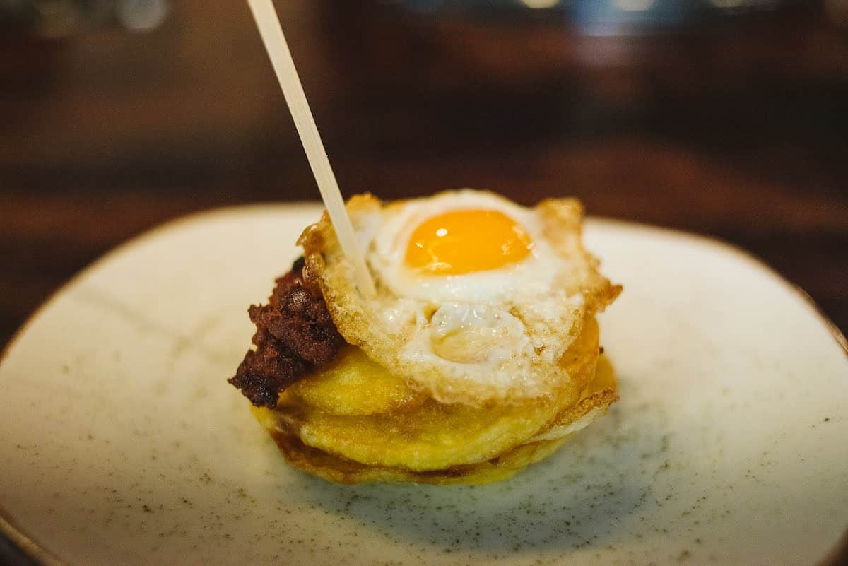 Stack of fried potato rounds topped with an egg and garnished with crumbled chorizo.