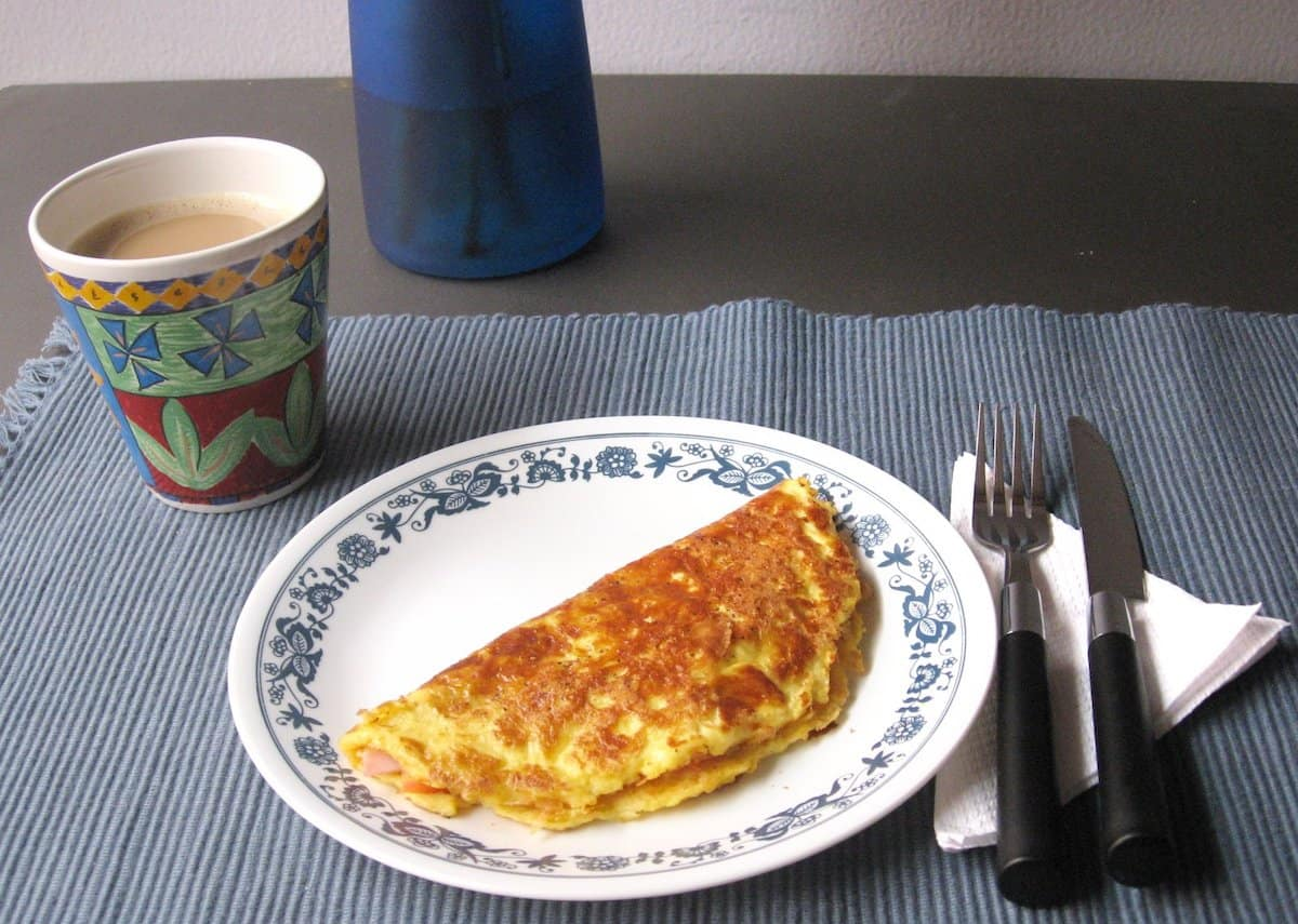 Omelet on a white plate on a table beside a fork, knife, napkin and a cup of coffee