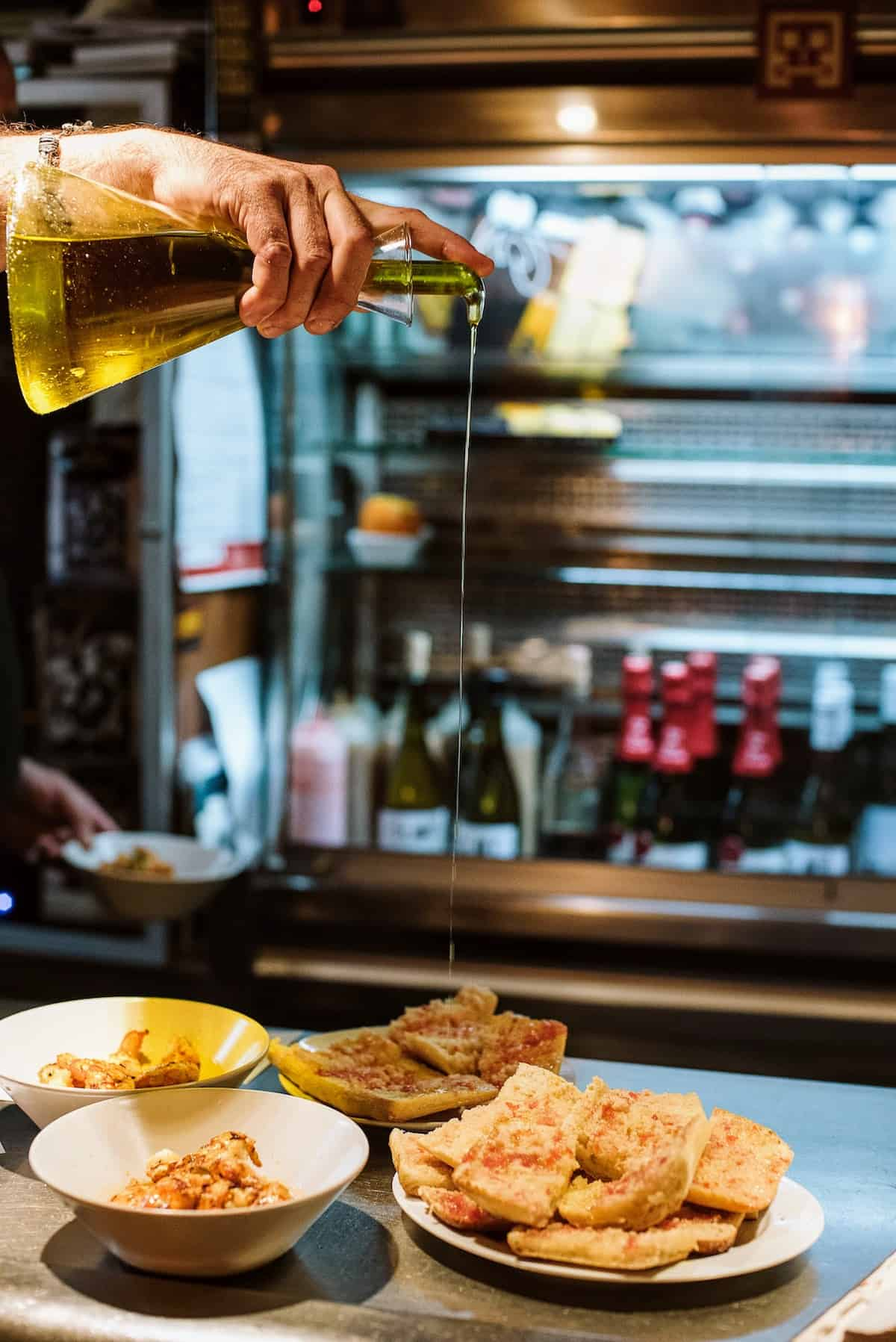 A hand pouring olive oil over a plate of toasted bread with tomato.