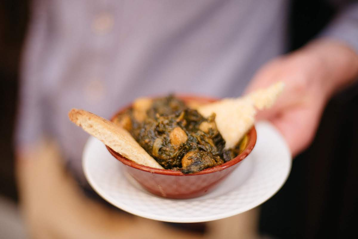 Small clay dish of spinach and chickpea stew served with crackers.