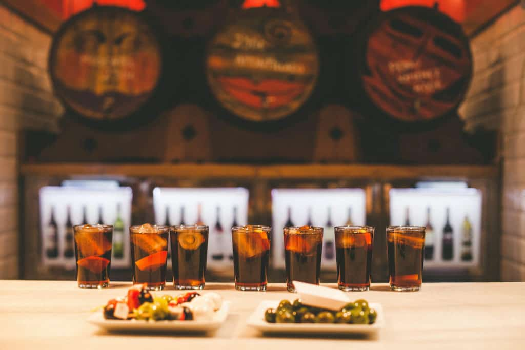 Seven glasses of vermouth, a plate of appetizer skewers, and a plate of olives on a bar top.