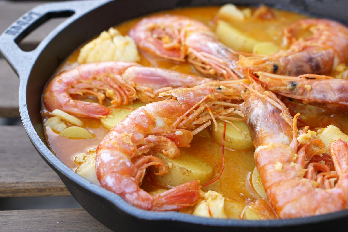 Seafood stew with jumbo unpeeled shrimp and potatoes in a large pan
