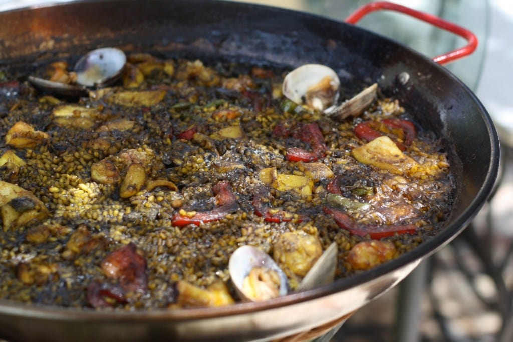 Large paella pan filled with black paella with monkfish, clams, and roasted peppers.