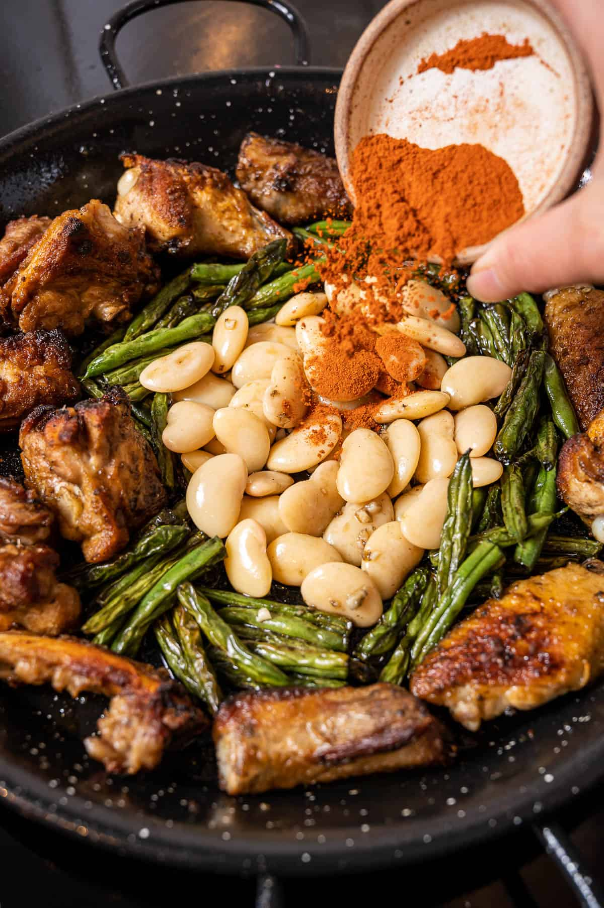 Close up of a person's hand pouring paprika into a pot of meat, veggies, and beans.