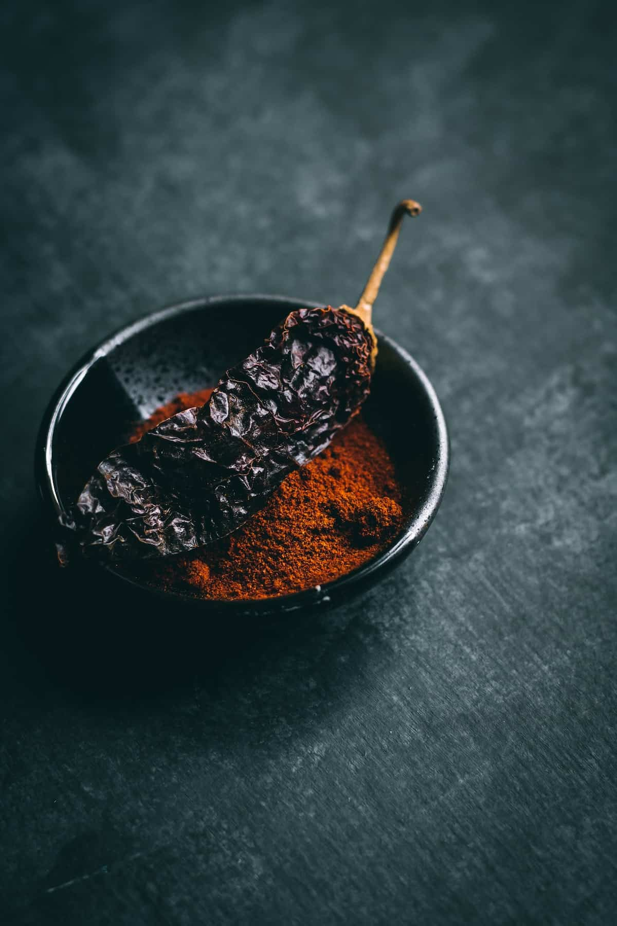 Shot of paprika and a dried pepper against a dark background.