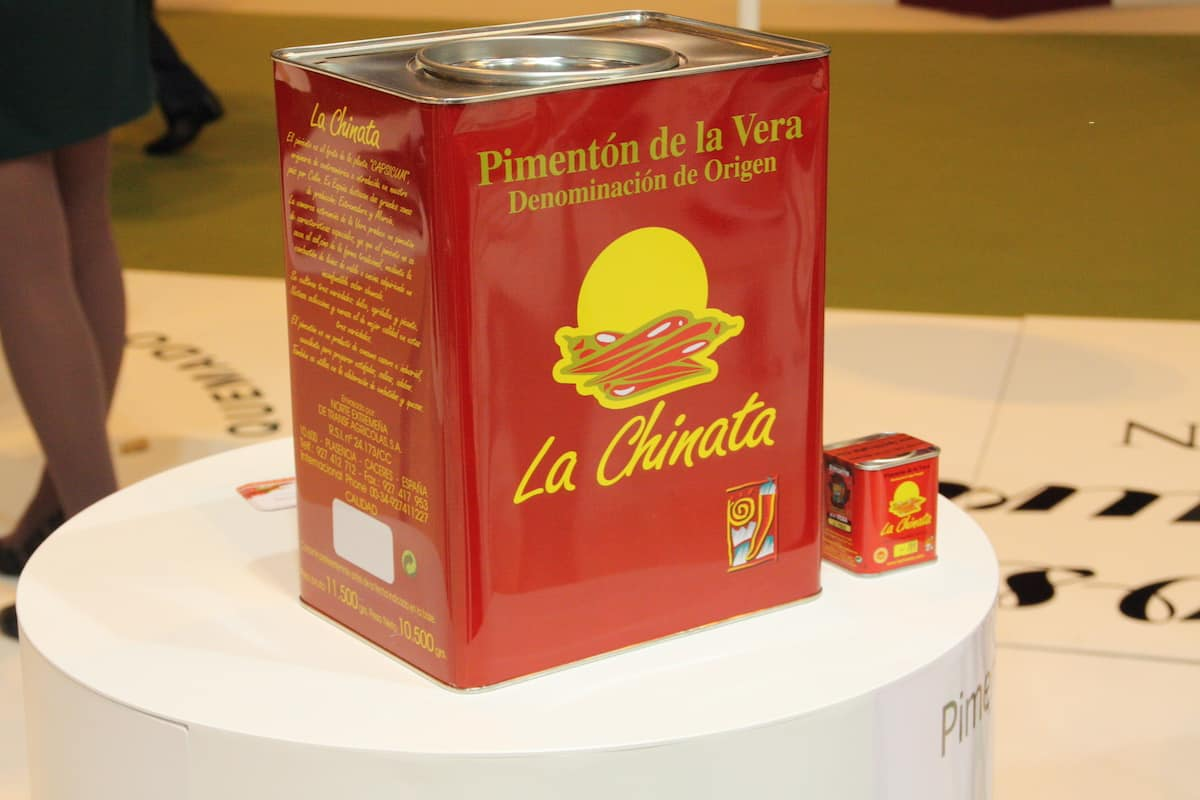 Large red and yellow container of paprika next to a smaller version of the same package.