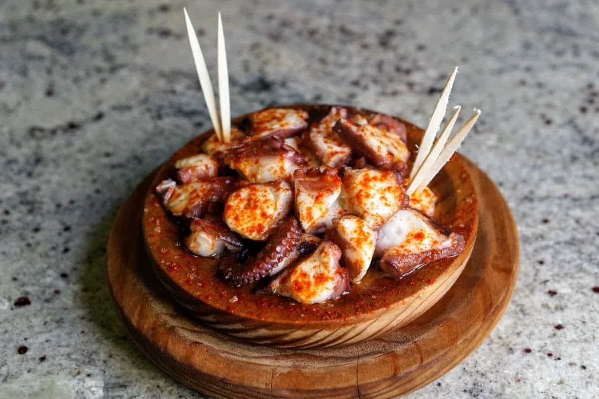 Slices of boiled octopus covered in paprika served in a clay dish with toothpicks.