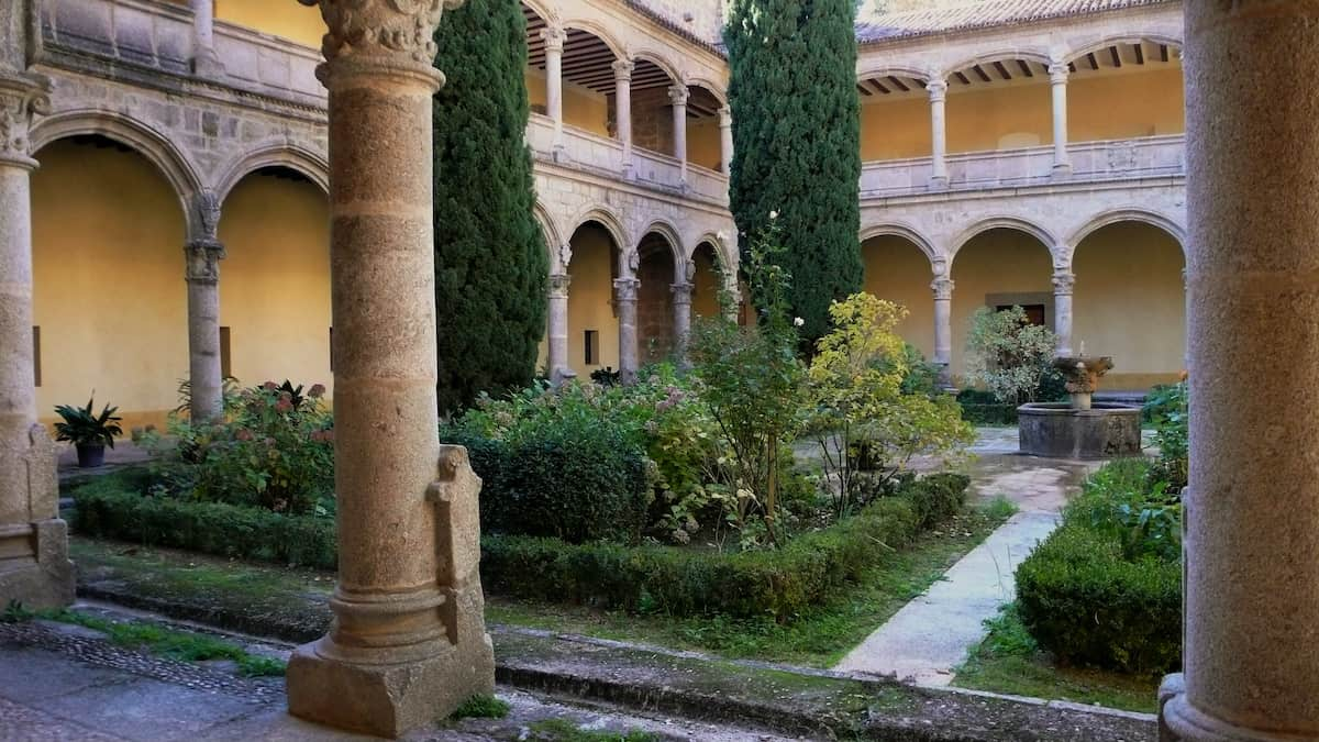 Interior courtyard of an old monastery full of green plants and surrounded by archways.