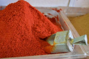 Smoked paprika sold in bulk at a spice store, with a metal scoop
