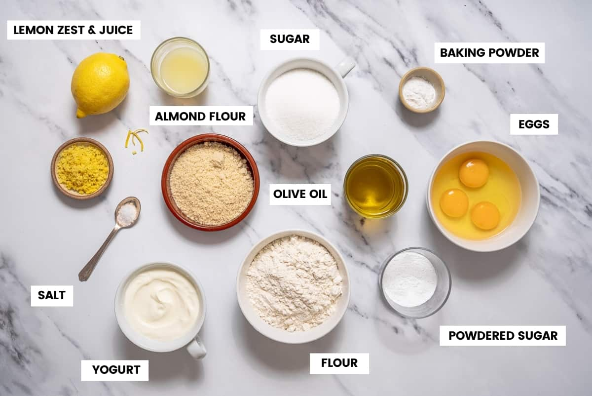 Lemon olive oil cake ingredients on a white marble countertop