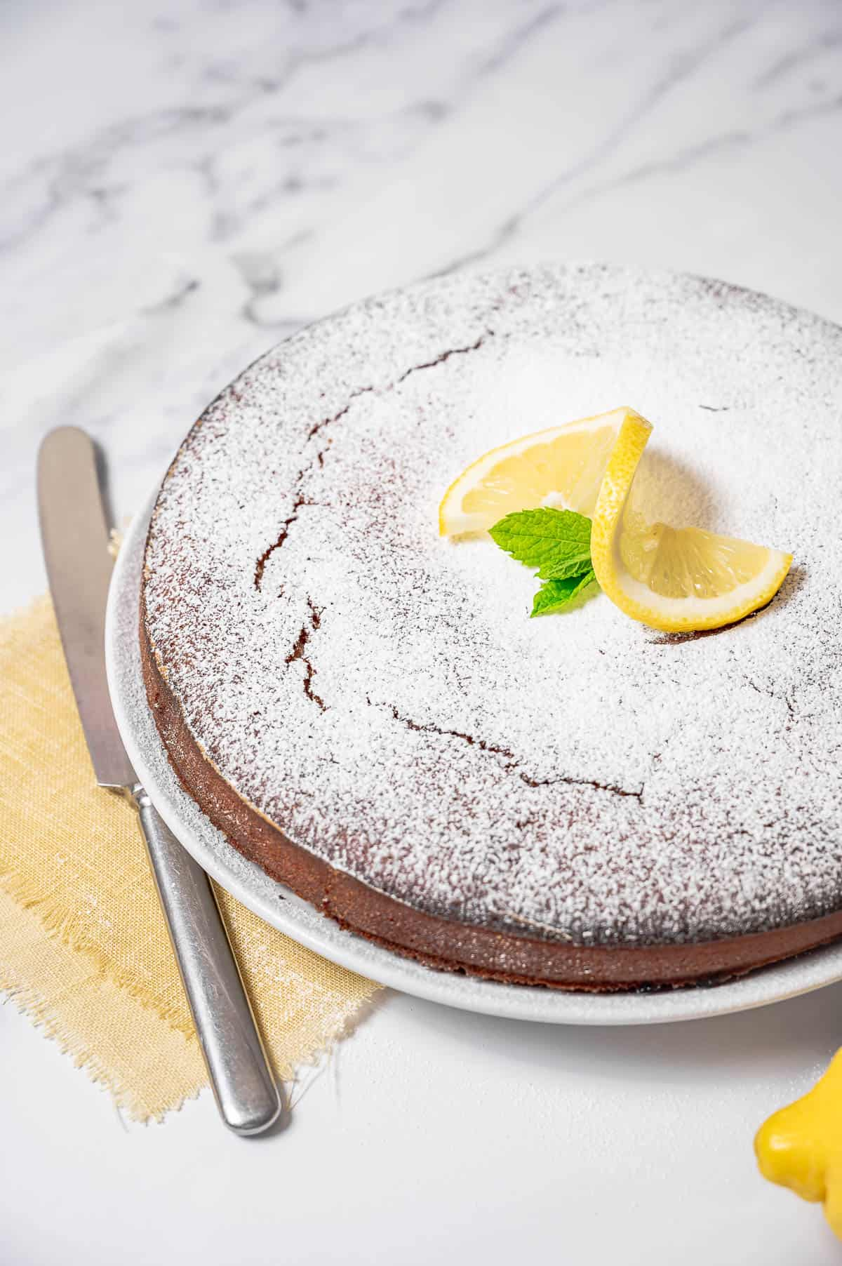 Lemon olive oil cake with almonds on a white cake dish topped with sliced lemon