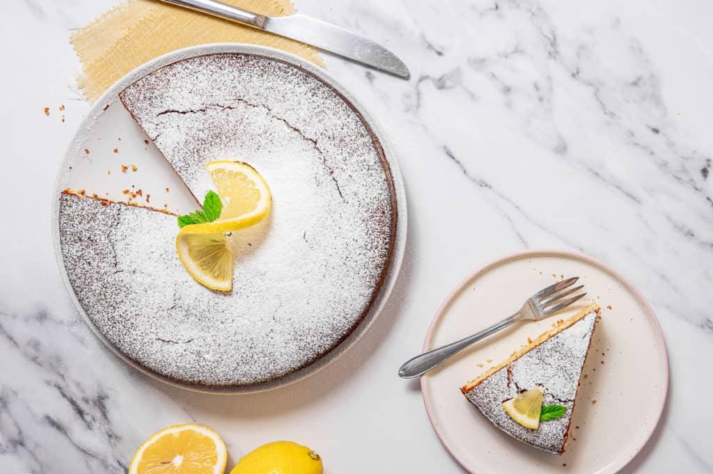 Overhead shot of lemon olive oil cake with one slice missing.
