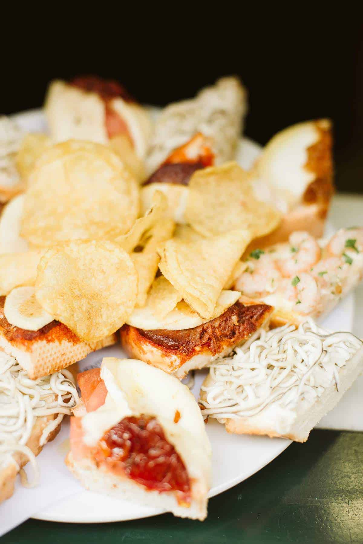 Tray of small open-faced sandwiches with potato chips in the middle