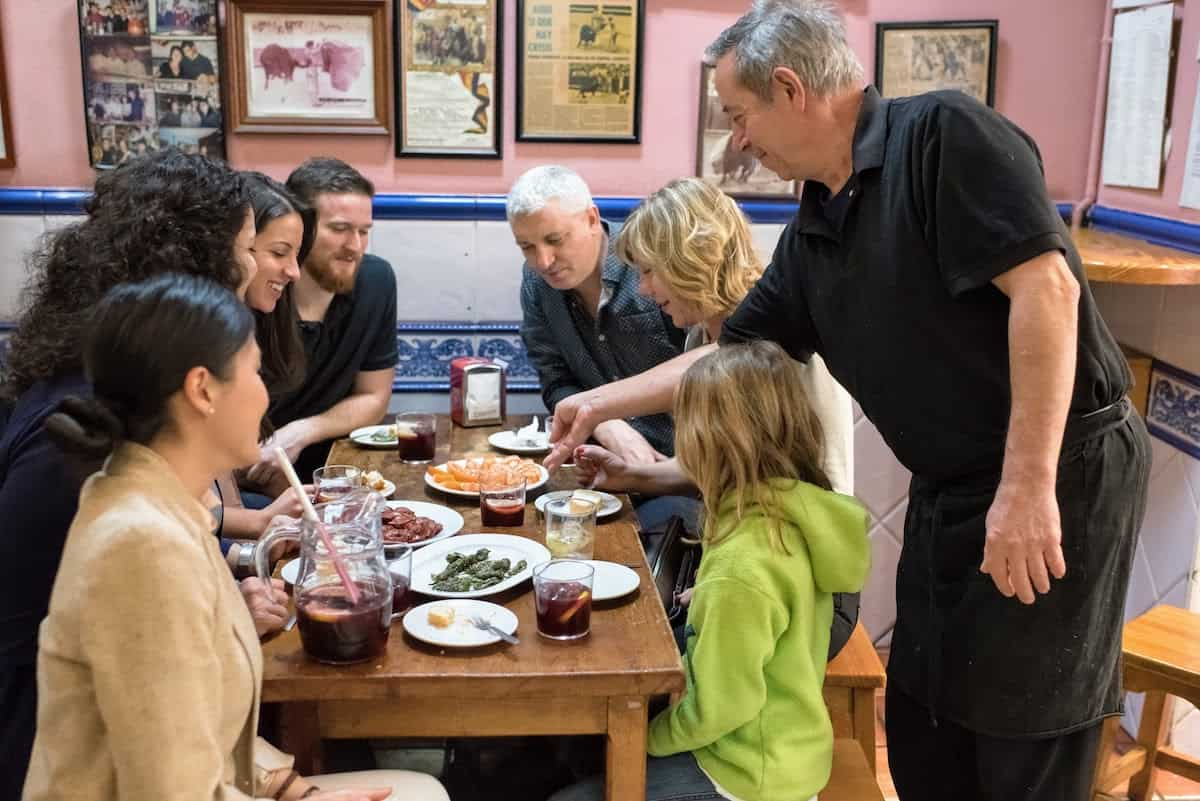 A family with kids seated around a small table covered in shared plates of Spanish food as a waiter sets down another dish.