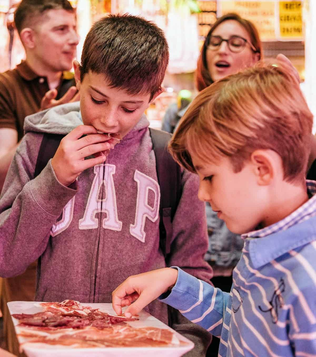 Two kids eating pieces of Spanish charcuterie off a white tray.