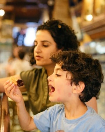 Mother and child sitting at a wooden bar eating churros and chocolate