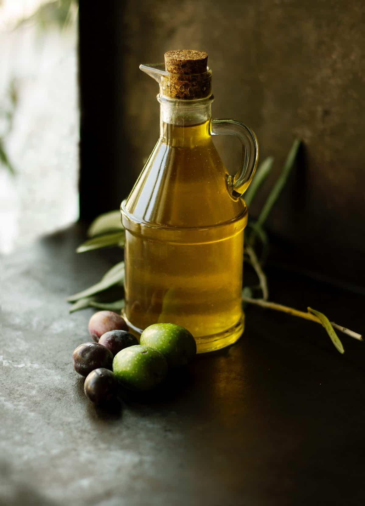 Clear bottle of olive oil and a handful of olives atop a dark surface.