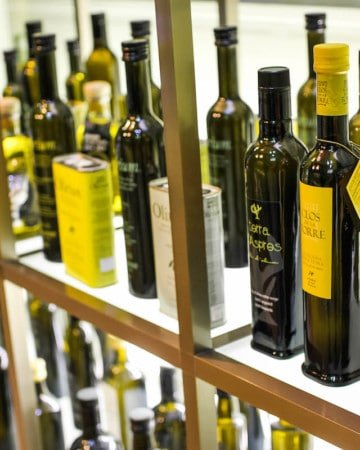 Many bottles of olive oil on a store shelf.
