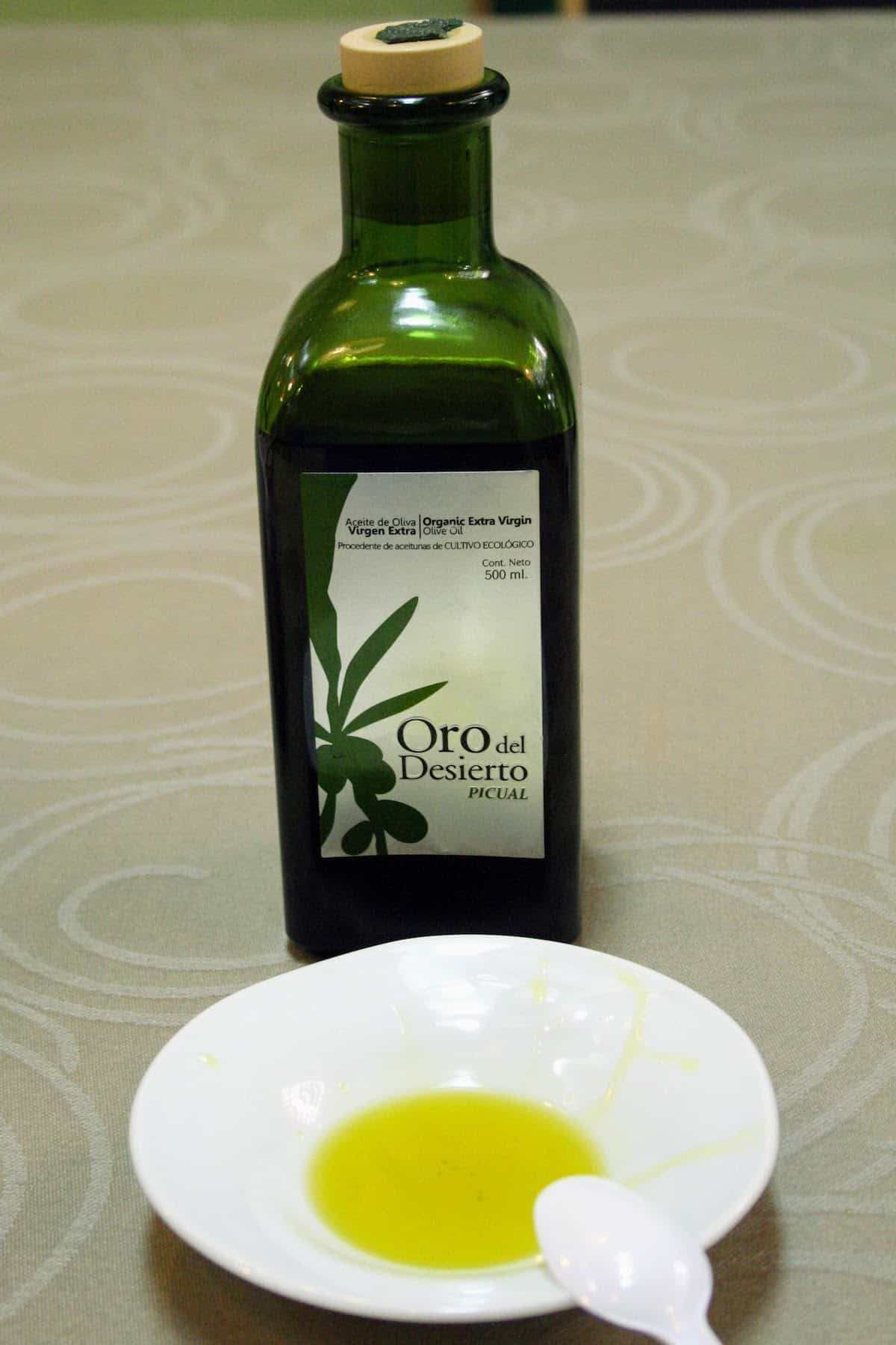 Bottle of olive oil behind a small white dish with a small amount of oil poured in.