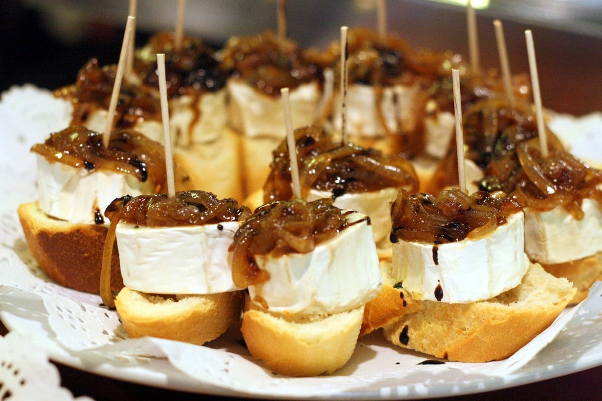 Small pieces of crusty bread topped with goat cheese and caramelized onions, all held together with a toothpick.