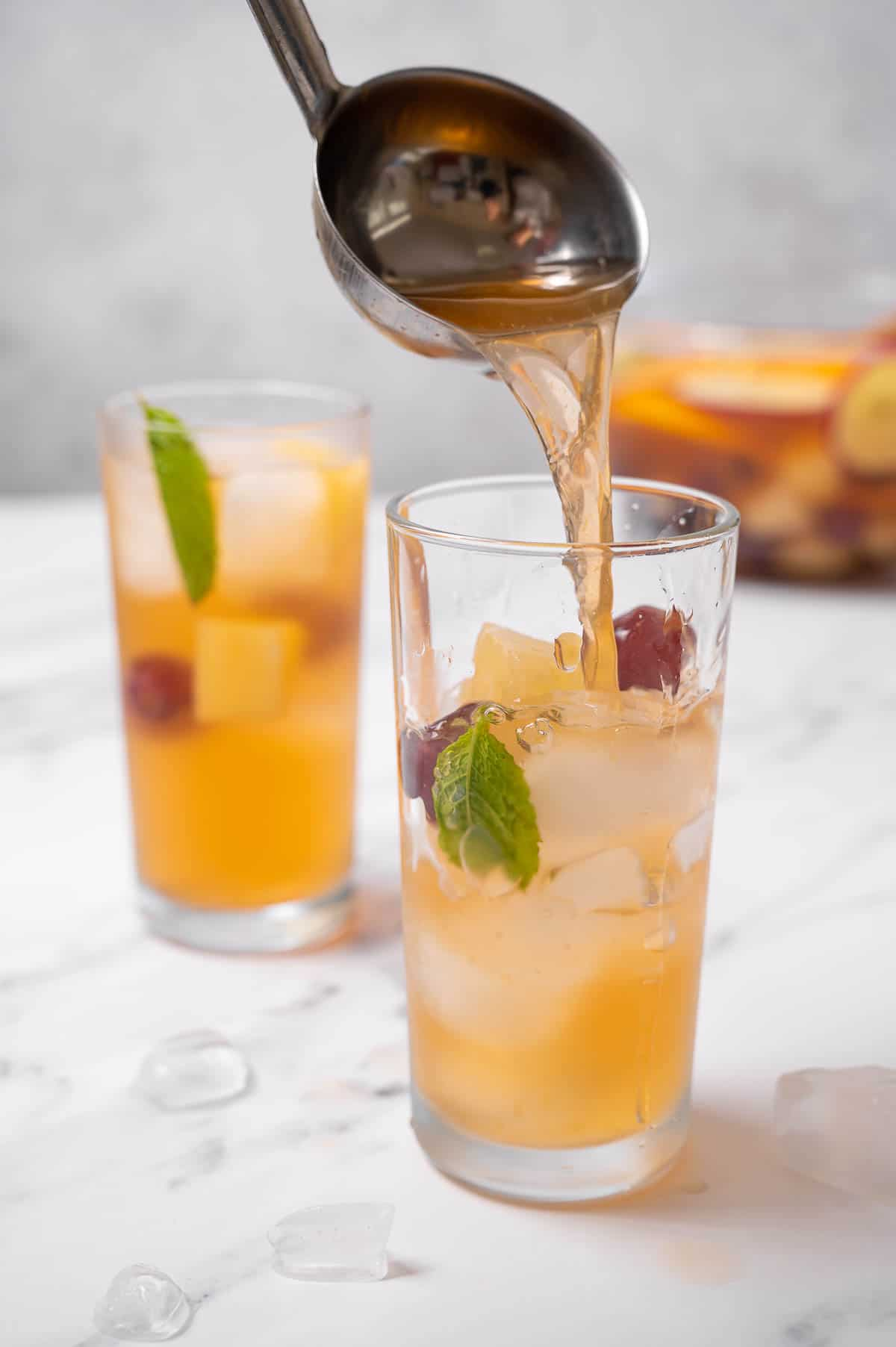 Two glasses of cava sangria being served from a ladle