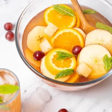 Cava Sangria in a punch bowl with orange and apple slices