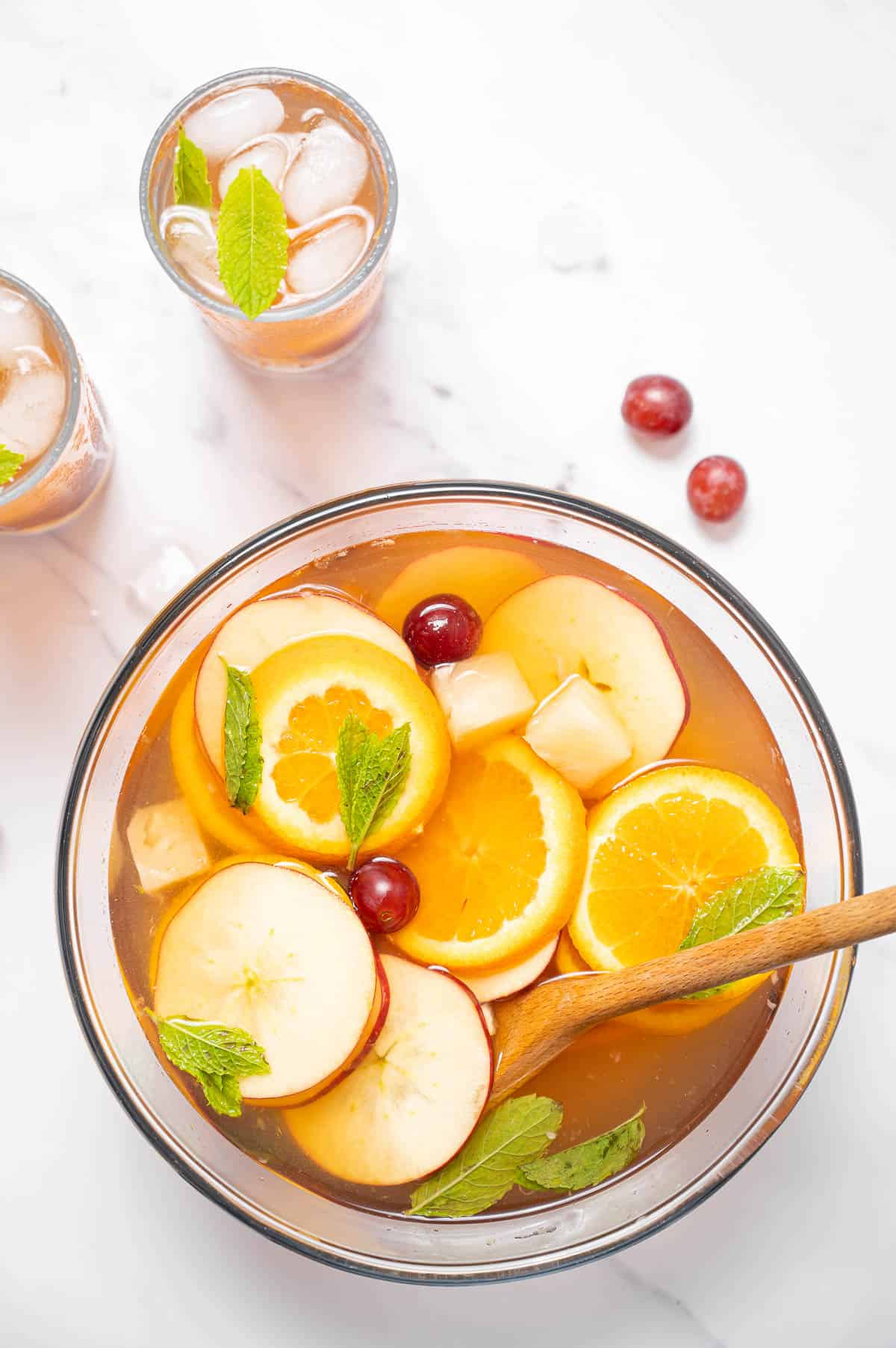 A punch bowl filled with cava sangria. Apple, orange and mint floating on top with a wooden spoon and two glasses in the background.