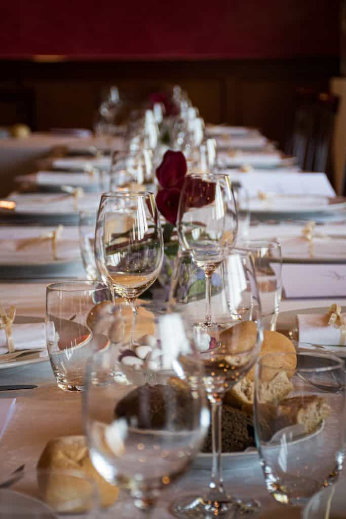 Vertical shot of a Christmas dinner table with place settings and wine glasses