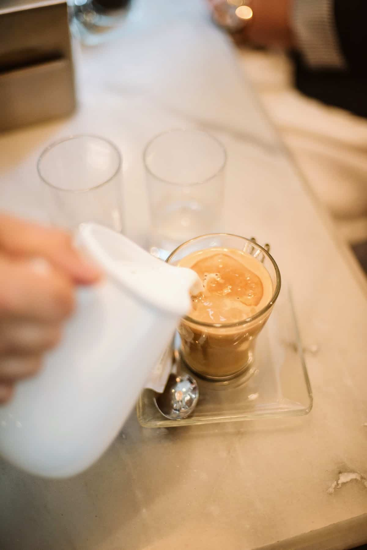 Overhead shot of a person pouring milk into a clear glass of coffee.