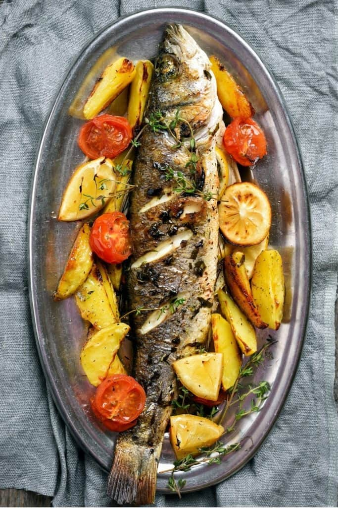 Roasted fish with lemon, tomato and potatoes on an aluminum platter