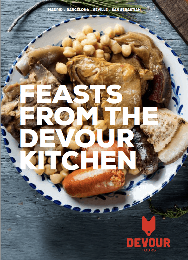 Cookbook cover reading Spanish Feasts from the Devour Tours Kitchen on top of a Spanish stew photo