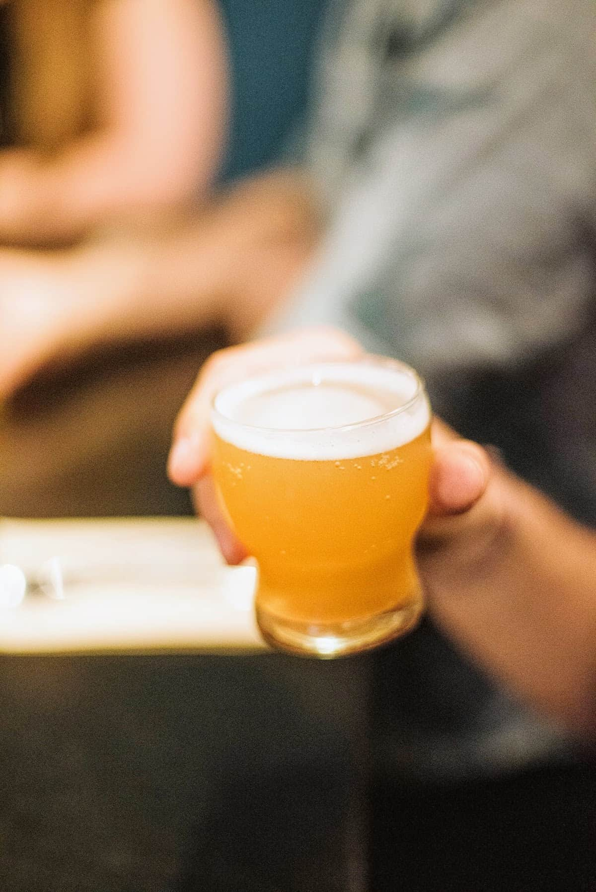 Close up of a person's hand holding a small draft beer