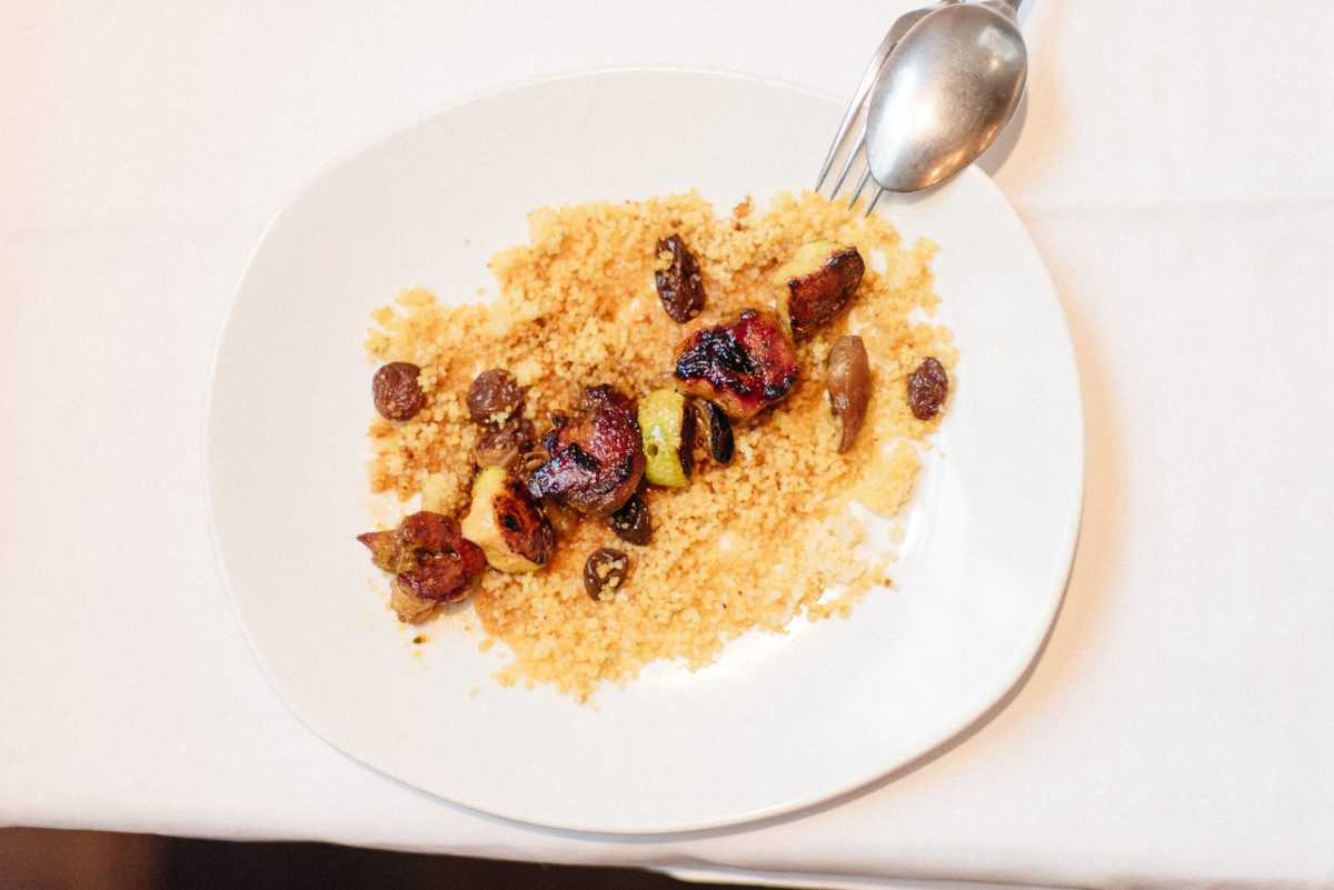 Grilled lamb with zucchini and dates served over cous cous on a white plate.