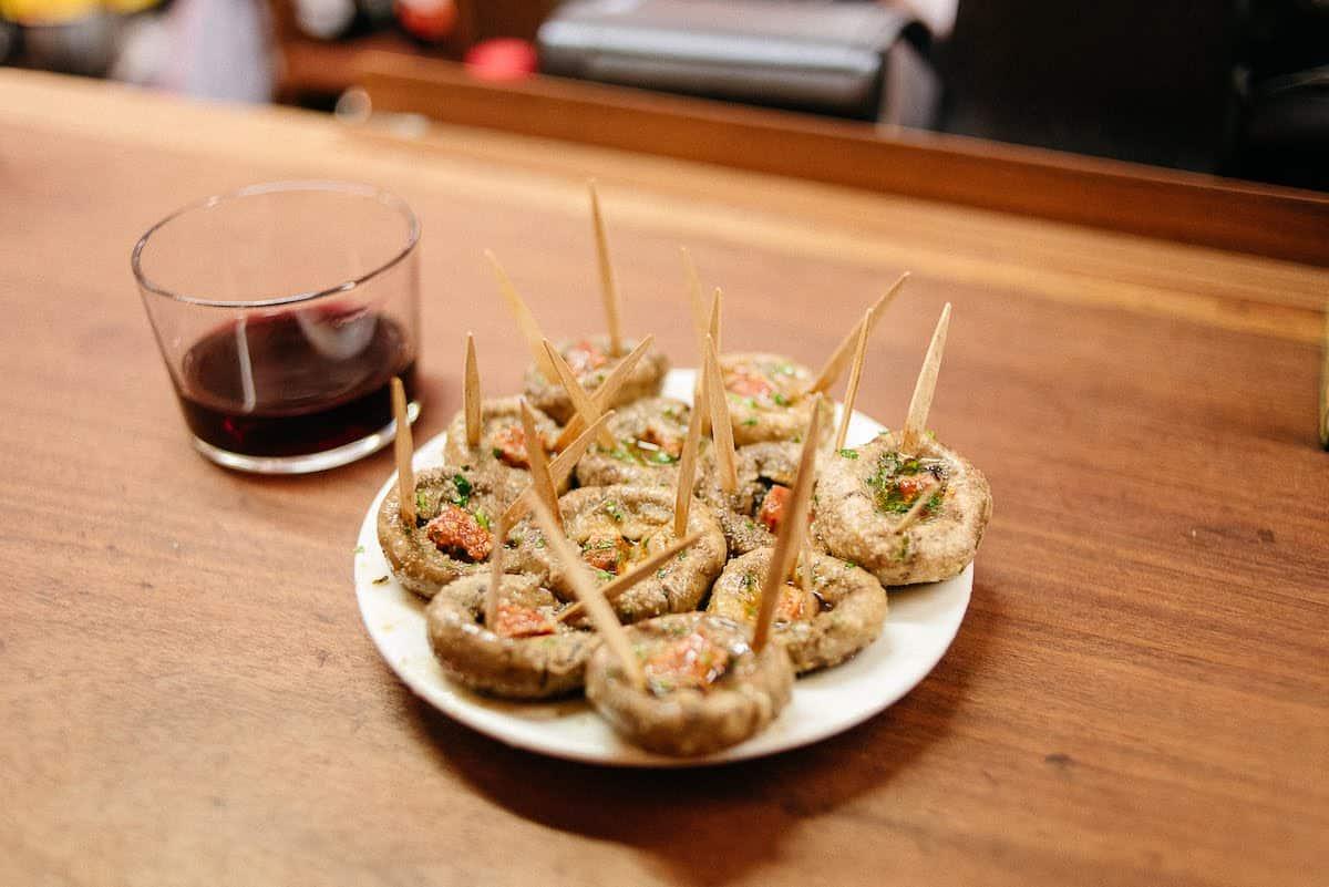 Chorizo-stuffed mushrooms on a white plate beside a short glass of red wine.