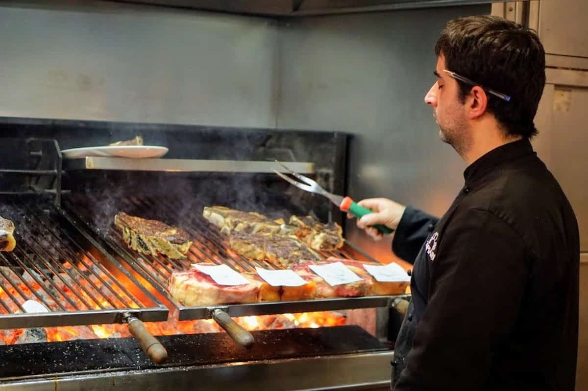 A man grilling steaks over a large charcoal grill.