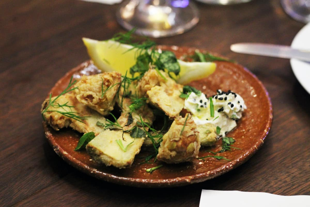 Tapas style dish garnished with lemon and herbs on a clay plate.
