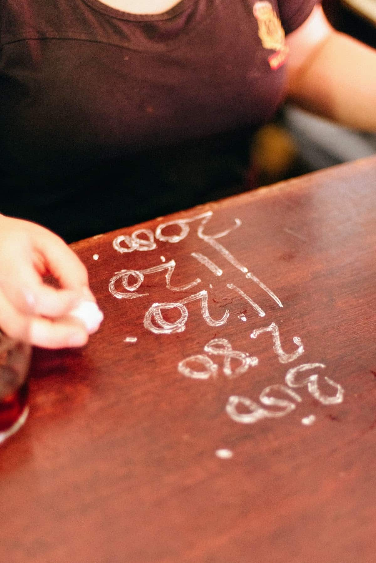 Close up of a bartender writing a client's tab in chalk on a wooden bar top.