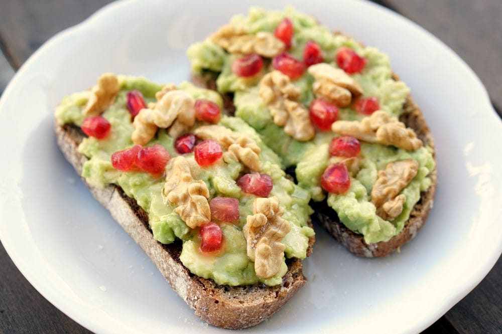 Delicious avocado toast recipe with pomegranate seeds and walnuts.