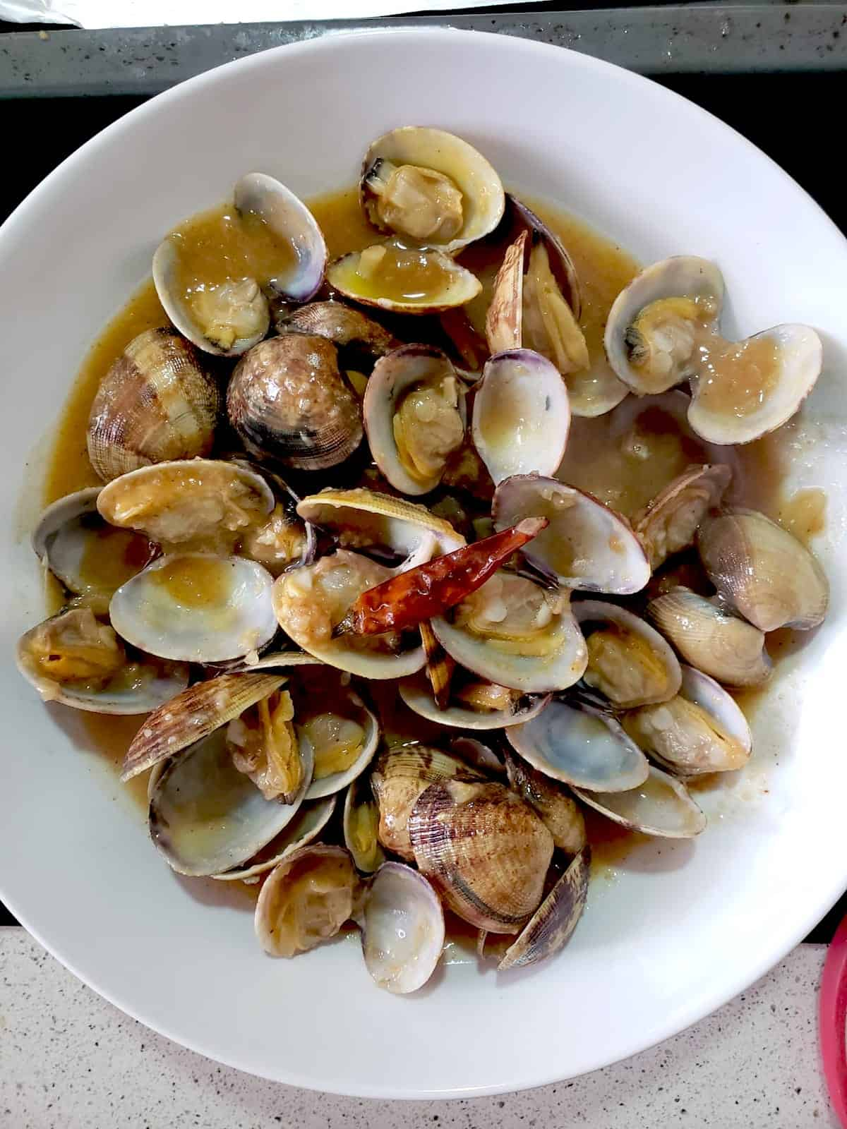 Overhead shot of small cooked clams in a white bowl