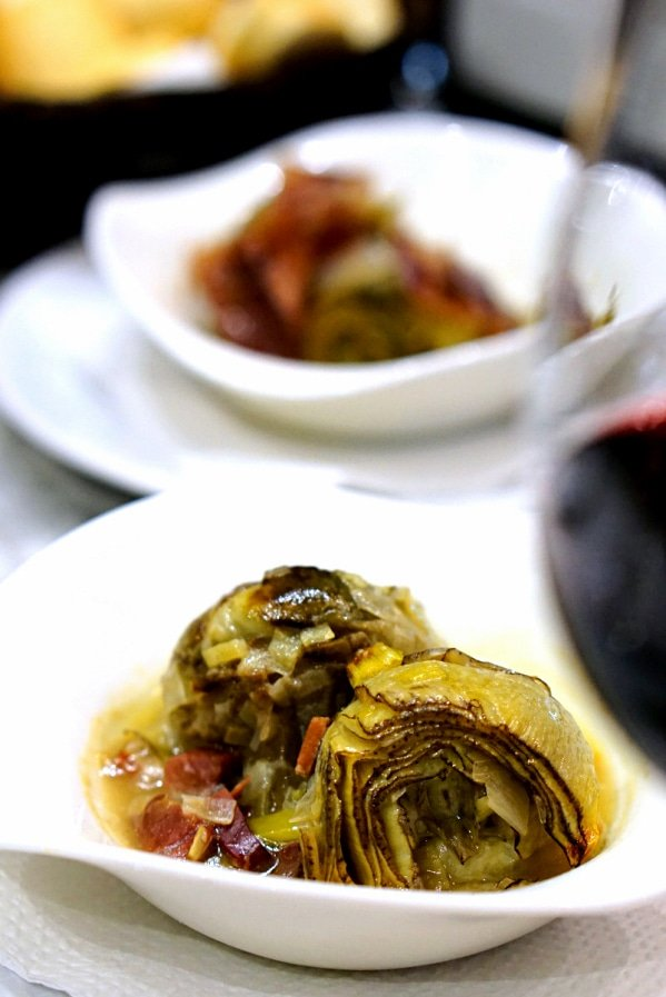The delicious artichoke tapas and of course, red wine at Mesón Mariano, one of the best traditional tapas bars in Malaga!