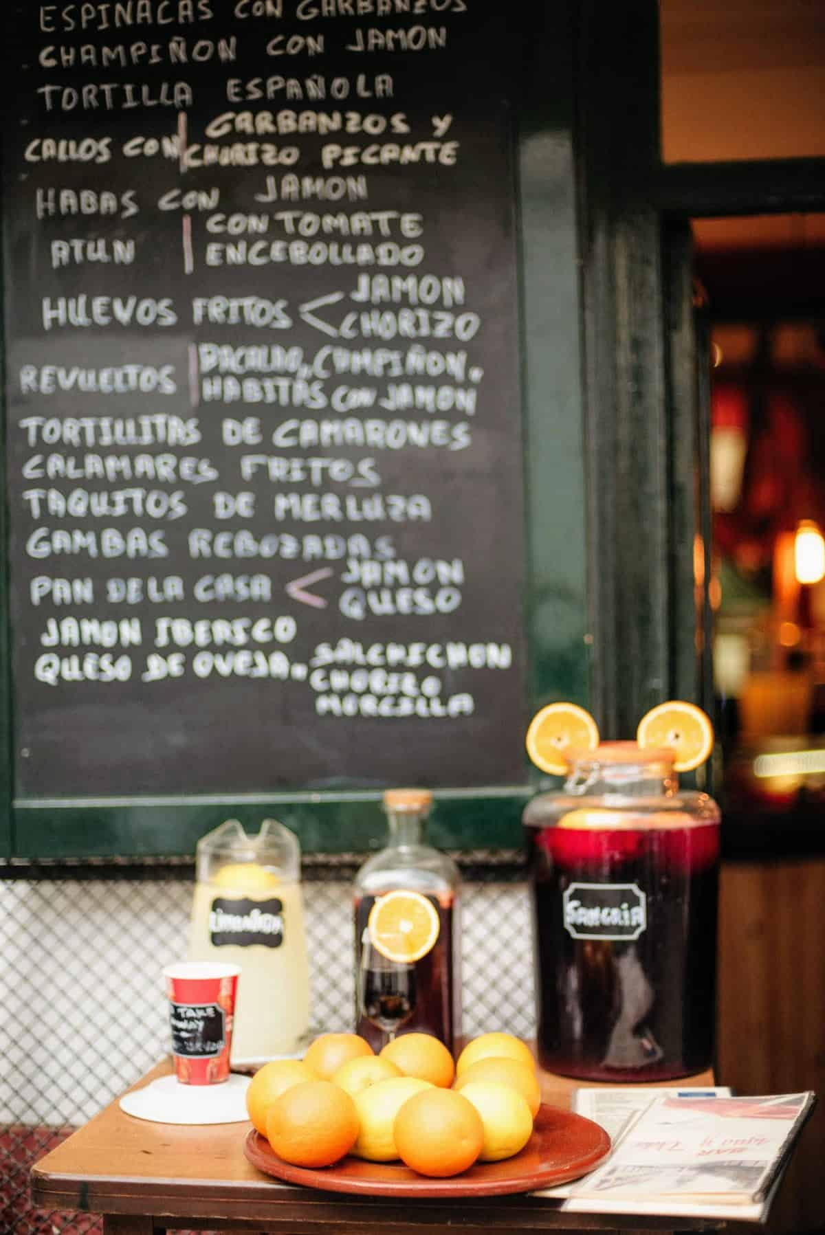 Large jugs of sangria and lemonade behind a tray of oranges, with a chalkboard menu in the background.