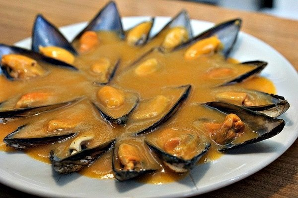 Mussels in garlic sauce are a Galician delicacy. Sample some of the best flavors in Santiago on one of our favorite terraces in Santiago.