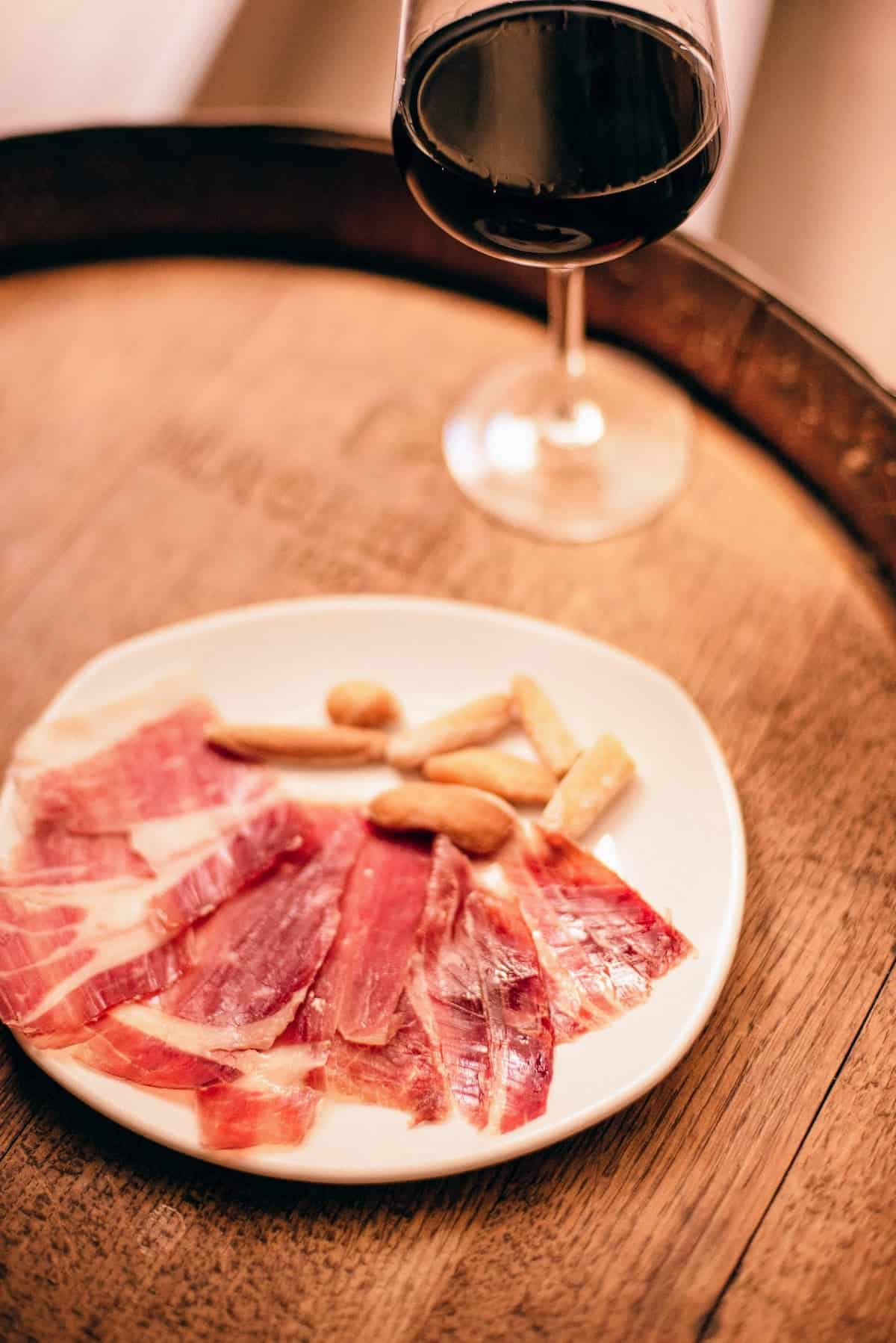 Cured ham slices and breadstick crackers on a white plate beside a glass of red wine atop a wooden barrel
