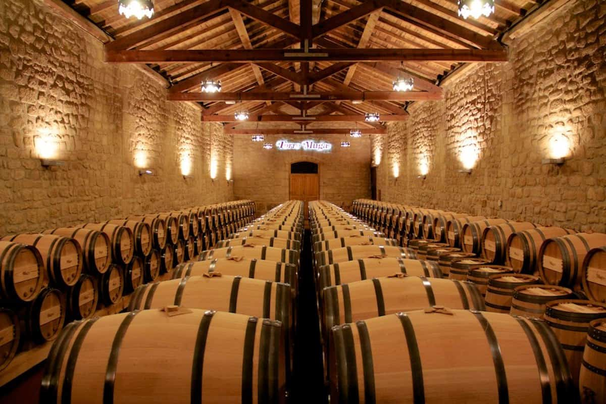Wooden wine barrels in an aging room with stone walls and high wooden beams supporting the ceilings