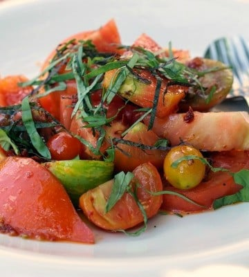 A tomato salad topped with greens—just one example of some of the fabulous vegan and vegetarian food in Santiago de Compostela!